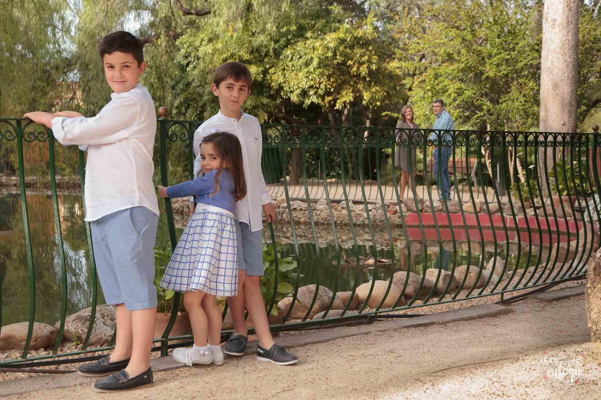 niño de comunión con sus hermanos en parque de Valencia