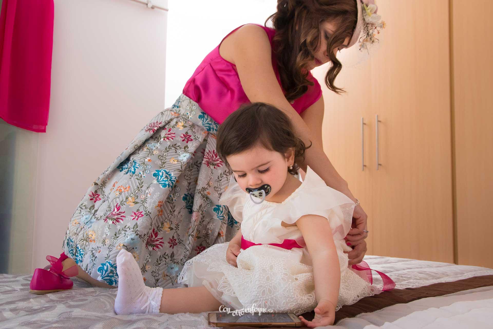 boda civil en Valencia. Novia vistiendo a su hija para la boda