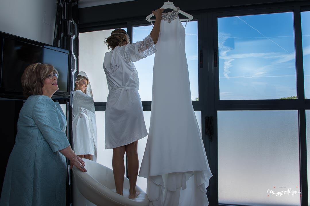 la novia con su bata descuelga su vestido de novia junto a su madre